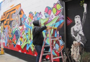 Juan Pineda, one of the graffiti artists participating in the Hello my name is show works on a piece on The Fridge exterior