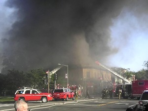 Smoke envelopes the building as fire officials arrive
