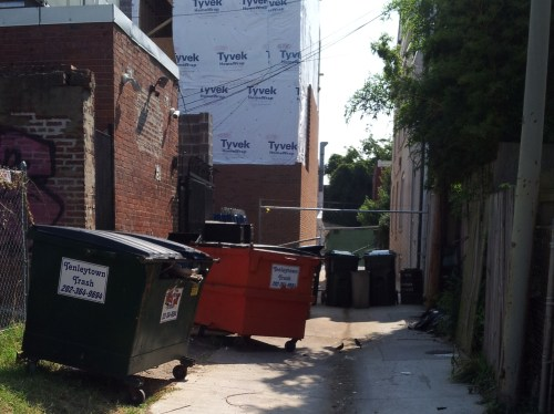 Conditions in an H Street alley last summer.  The fence has been removed but trucks displaced by street cars must use the alley for deliveries to H Street restaurants.