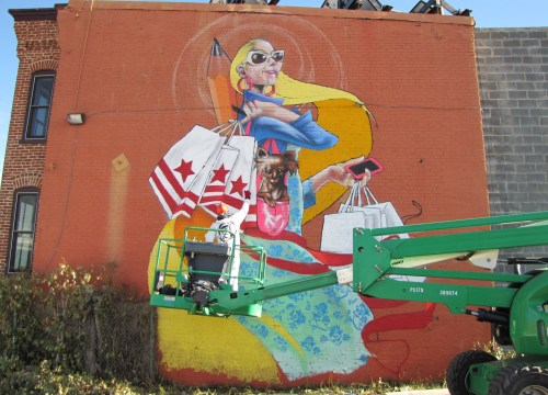 Mural promoting local shopping overlooks the building site.