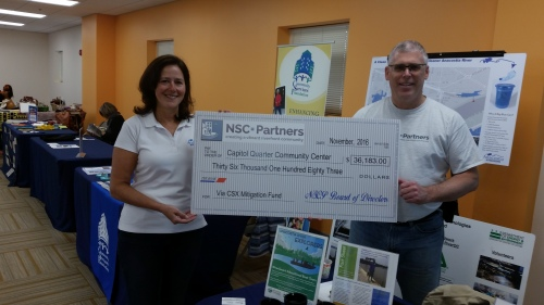Bruce DarConte and Emily Franc with a check for $36183 for purchasing equipment presented to the Community Center on Saturday.  The funding comes from the benefits and amenities package the community received from CSX as compensation for the impact of reconstruction of the CSX tunnel.  DarConte is Founder and President of Near Southeast Community Partners, http://www.nscpartners.org/  a 501c3 nonprofit – which is the vehicle through which CSX Tunnel Community Benefits are distributed to the community.  Emily Franc heads up Anacostia Riverkeeper  http://bit.ly/2fhwkxp